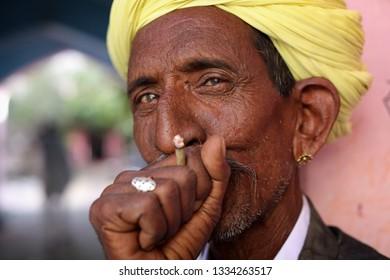 PUSHKAR, INDIA - NOVEMBER 14, 2018: Unidentified Rabari tribal man smokes a bidi at the Pushkar Camel Fair, Rajasthan. The fair is the largest camel fair in India.