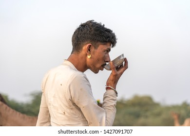 PUSHKAR, INDIA - NOVEMBER 14, 2018 : Indian man is drinking camel milk in the desert Thar during Pushkar Camel Mela, Pushkar, Rajasthan, India. This fair is largest camel trading fair in the world.
