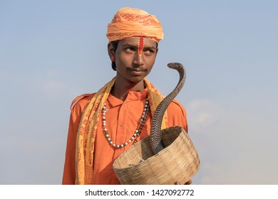 PUSHKAR, INDIA - NOVEMBER 14, 2018 : Hindu sadhu holy man and snake cobra in the desert Thar on time Pushkar Camel Mela near holy city Pushkar, Rajasthan, India, close up portrait