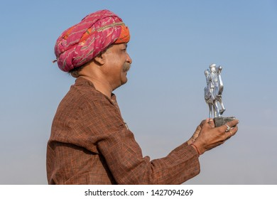 PUSHKAR, INDIA - NOVEMBER 14, 2018 : Indian man sells souvenirs in the desert Thar during Pushkar Camel Mela near holy city Pushkar, Rajasthan, India