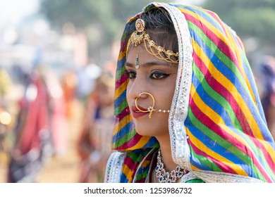 PUSHKAR, INDIA - NOVEMBER 16, 2018 : Indian young girl in the desert Thar on time Pushkar Camel Mela near holy city Pushkar, Rajasthan, India, close up portrait