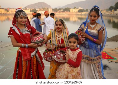 PUSHKAR, INDIA - NOVEMBER 16, 2018: Unidentified girls in traditional dresses at the Deep Daan Aarti of the Pushkar Camel Fair, Rajasthan. The fair is the largest camel fair in India.