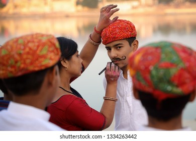 PUSHKAR, INDIA - NOVEMBER 16, 2018: Unidentified boys in traditional dresses at the Deep Daan Aarti of the Pushkar Camel Fair, Rajasthan. The fair is the largest camel fair in India.