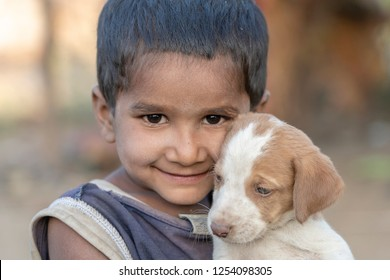 PUSHKAR, INDIA - NOVEMBER 17, 2018 : Indian poor child with small dog in the desert Thar on time Pushkar Camel Mela near holy city Pushkar, Rajasthan, India, close up portrait