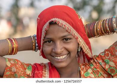 PUSHKAR, INDIA - NOVEMBER 17, 2018 : Indian young girl in the desert Thar on time Pushkar Camel Mela near holy city Pushkar, Rajasthan, India, close up portrait