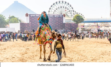 PUSHKAR, INDIA - NOVEMBER 23, 2018: Unidentified tourists enjoying camel ride at Pushkar Camel fair near holy city of Pushkar, Rajasthan, India.