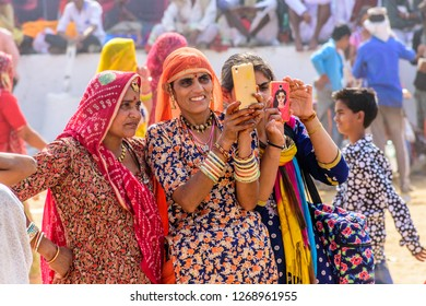 PUSHKAR, INDIA - NOVEMBER 23, 2018 : Unidentified local women wearing traditional cloths are taking selfies during the Pushkar Camel fair near holy city Pushkar, Rajasthan, India.