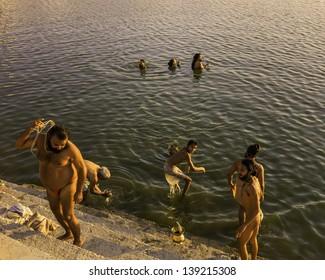 PUSHKAR, INDIA - OCTOBER 24: Hindu men take a ritual bath in the holy lake during Purnima, phase of full moon, on October 24, 2011 in Pushkar, Rajasthan, India.