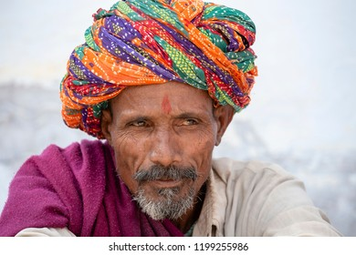 PUSHKAR, INDIA - OCTOBER 25, 2014: Unidentified Indian man, sits on the ghat along the sacred Sarovar lake in Pushkar. Indian men attended the Pushkar Camel Mela
