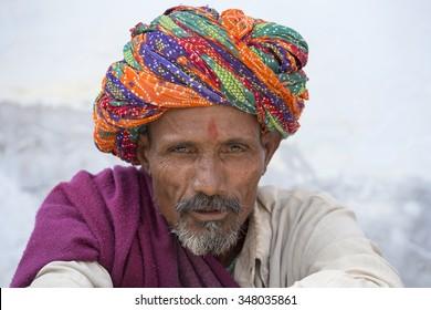 PUSHKAR, INDIA - OCTOBER 25, 2014: Unidentified Indian man, sits on the ghat along the sacred Sarovar lake. Pushkar - famous worship place in India