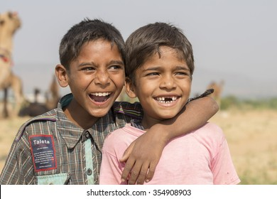 PUSHKAR, INDIA - OCTOBER 26, 2014 : Unknown two young happy boy involved in Pushkar Camel Mela. Pushkar Camel Fair is the largest camel trading fair in the world