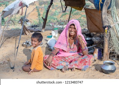 PUSHKAR, INDIA - OCTOBER 27, 2014: Unidentified woman and child at the attended the annual Pushkar Camel Mela. This fair is the largest camel trading fair in the world.