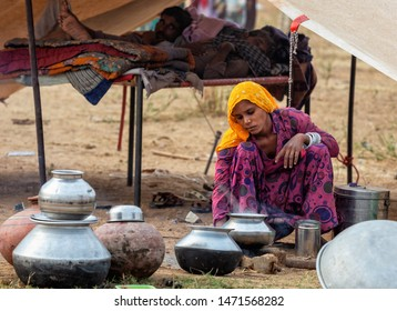 Pushkar, India - October 31, 2014: Traditionally dressed unidentified  indian tribal woman sits in front of the tent she lives and washes the dishes during Pushkar camel fare
