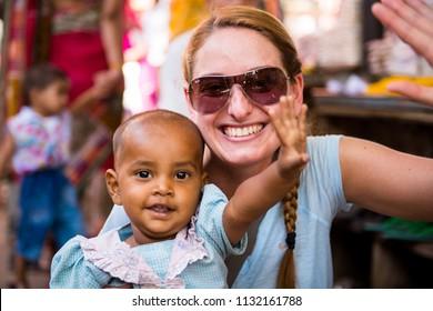 Pushkar, Rajastan / India - May 30 2013: Caucasian woman having fun with local indian little girl