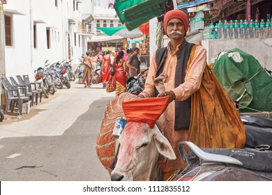Pushkar, Rajasthan / India - 06 10 2018: A Hindu devotee standing on a street with his cow who has a extra extremity which is considered holy.
