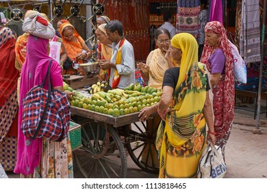 Pushkar, Rajasthan / India - 06 10 2018: People standing around the mango stand in the main market area in Pushkar on a hot summer day.