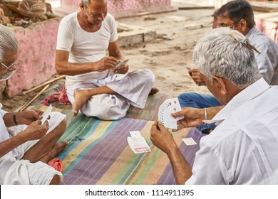 Pushkar, Rajasthan / India - 06 16 2018: Group of old men playing cards during a hot afternnon in the citys main market area.