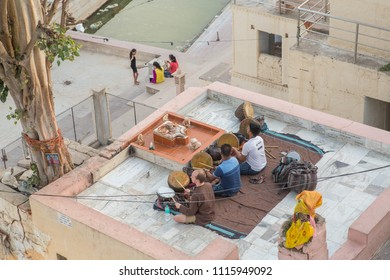 Pushkar, Rajasthan / India - 06 17 2018: Top view of two Indian men and one foreigner playing the drums by the city lake at sunset.