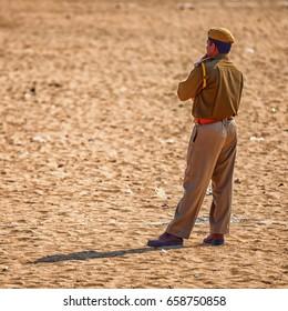PUSHKAR, RAJASTHAN, INDIA - CIRCA NOV 2012: Traditional Fair in Pushkar. A police officer keeps order