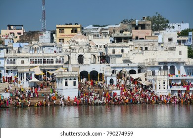 PUSHKAR, RAJASTHAN, INDIA - NOVEMBER 2, 2006: Hindu pilgrims bathing in sacred Lake Pushkar on ghats. Countless people in colourful attire gather to take a dip in the Holy Lake and pray to deities.