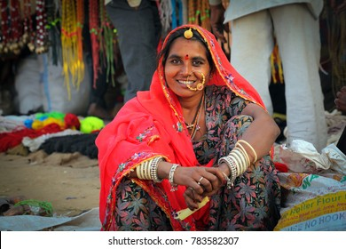 Pushkar, Rajasthan, India - November 24, 2012 : An unidentified Rajasthani Indian woman dressed in colorful attire pose for camera at Pushkar camel Fair (Pushkar Mela)