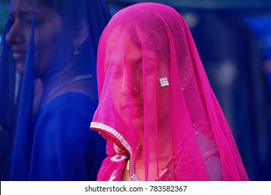 Pushkar, Rajasthan, India - November 24, 2012 : A beautiful Rajasthani Indian woman in veil and dressed in colorful attire attends the Pushkar camel Fair (Pushkar Mela)