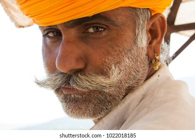 Pushkar, Rajasthan, India - November 5 2014 : Close up portrait of Indian man in saffron colored turban at the Camel Fair in Pushkar