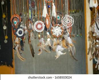 Pushkar, Rajasthan / India - November 5, 2019 : Feather Pendants lockets necklace hanging in Shop