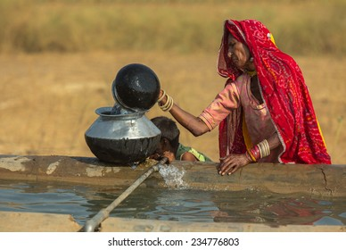 PUSHKAR,INDIA - November 3,2014 : Unidentified women draw water form the well and take it to her tent in desert near Pushkar,India