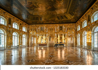 Pushkin, Russia - September 11 2018: An ornate golden interior ballroom with a grand piano inside the Rococo Catherine Palace near St. Petersburg, Russia.