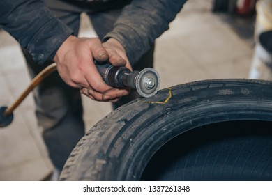 Pushkino, Russia 07 04 2018: the process of repairing the wheel on the car. The master cleans the surface of the tire with an iron brush.