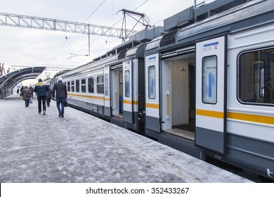 PUSHKINO, RUSSIA, on DECEMBER 17, 2015. Winter day. The suburban electric train stopped at a platform of the railway station. Passengers go on a platform