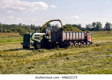 Pushkin,Russia-2 July:Russian KAMAZ truck collects grass clippings, which cuts the tractor driving by on the green field in the summer in Tsarskoye Selo in celebration of World UFO Day on 2 July,2016.