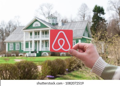 Pushkinskie Gory, Russia. May, 2018. Travel around the world with Airbnb. Logo Airbnb and the old beautiful house with green garden on the background.