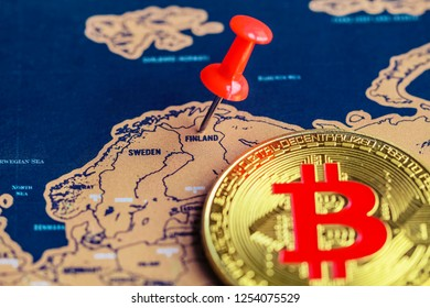 Pushpin and bitcoin on Finland part of world map. Investment in / mining of bitcoin in Finland concept.
