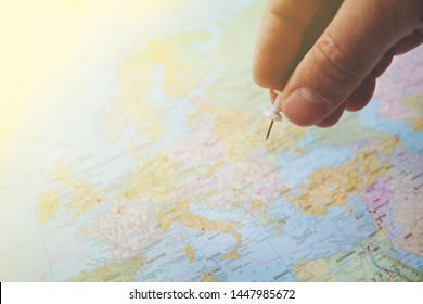 pushpin in hand over a blurred world map