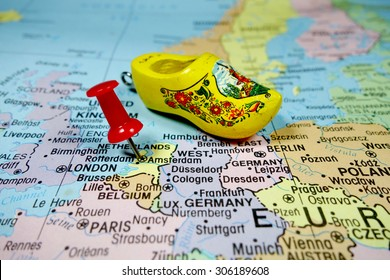 Pushpin marking on Amsterdam, Netherlands map with wooden shoe