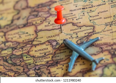 Pushpin and mini airplane on Ukraine part of world map. Travel to Ukraine concept. Selective focus.