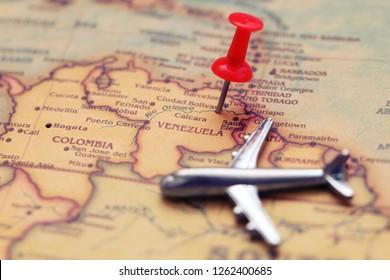 Pushpin and mini toy plane on Venezuela (map). Selective focus. Flights to Venezuela concept.