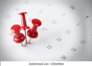Pushpins with bright light focused on calendar detail, Important date, business trip, or meeting appointment reminder concept image with selective focus