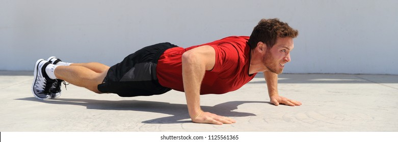 Pushup fitness man banner doing push-ups workout bodyweight exercise on gym floor. Athlete working out chest muscles strength training outdoors panoramic crop.