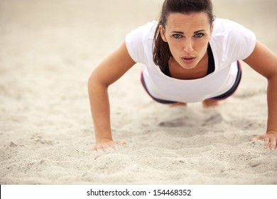 Push-ups fitness woman doing pushups outside on beach. Fit female sport model girl training crossfit outdoors. Caucasian athlete in her 20s.