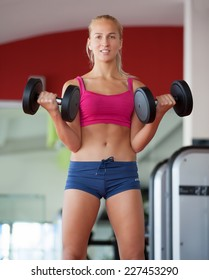 Push-ups woman with dumbbells workout fitness club at weightlifting gym