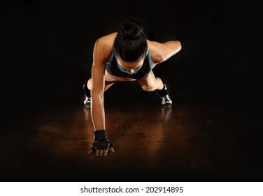 Pushup.Sporty girl doing exercise pushups on wooden floor,studio shot