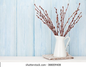 Pussy willow branches bouquet on shelf in front of wooden wall. View with copy space
