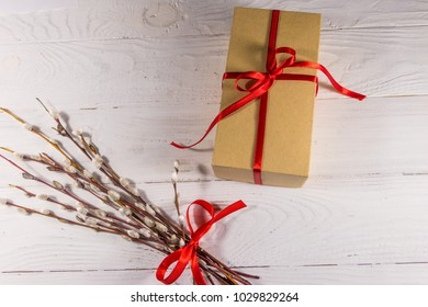 Pussy willow twigs and cardboard gift box on white wooden table. Top view