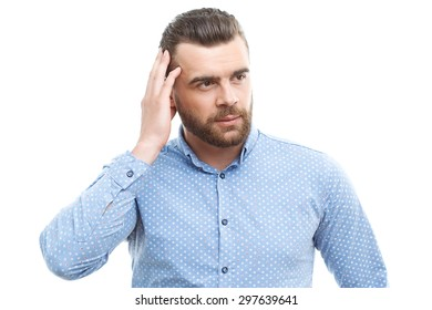 . Put on thinking cap. Attractive middle-aged man with beard touching his head with his fingers and looking aside isolated on white background.