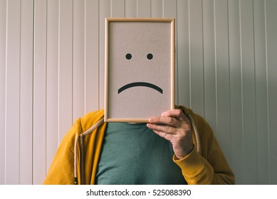 Put a sad pessimistic face on, sadness and depressive emotions concept, man holding picture frame with smiley emoticon printed.