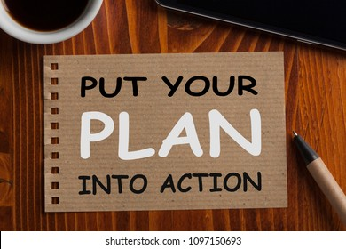 Put Your Plan Into Action written on recycled page note with pen, smartphone and cup of coffee.