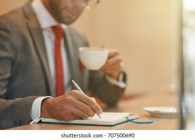 Put your thoughts in order. Close up of a confident businessman making notes and drinking coffee while resting in the cafe